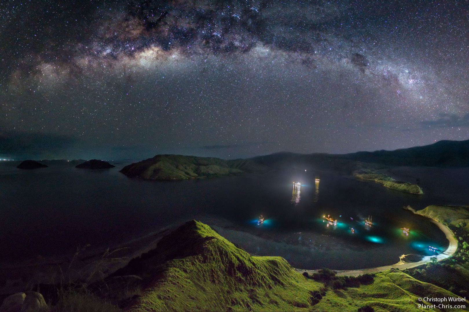 Lamps of divers in the water, the milky way above the waters of Komodo National Park, Indonesia